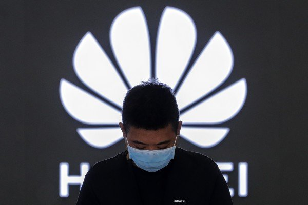 An employee wearing a face mask to help curb the spread of the coronavirus stands inside a Huawei flagship store in Beijing, March 31, 2021. Photo: AP