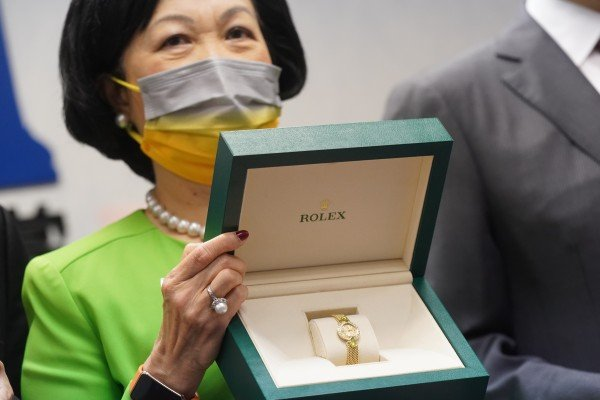 New People's Party chairwoman Regina Ip poses with a Rolex to be offered up in a lottery for vaccinated party allies. Photo: Sam Tsang