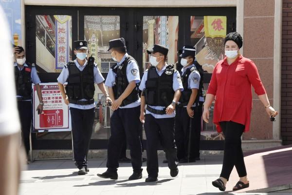 Police officers patrol near the International Grand Bazaar in Urumqi in China's Xinjiang Uygur autonomous region on July 5. Photo: Kyodo