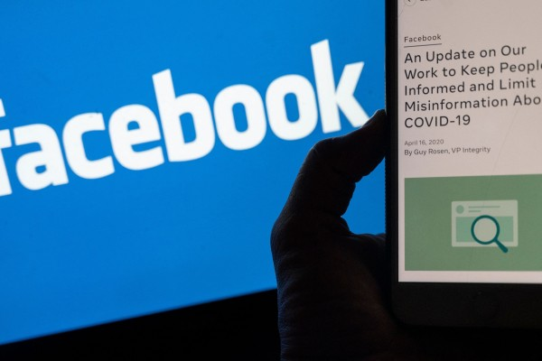A smartphone screen displays a new policy on Covid-19 misinformation with a Facebook website in the background. Photo: AFP