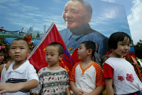 Kindergarten students stand in front of a billboard featuring a portrait of Deng Xiaoping in Shenzhen to mark the 100th anniversary of the birth of the late paramount leader on August 22, 2004. The city, one of the youngest in China, is set to become the first in the country to guarantee spots for children in local kindergartens. Photo: Reuters