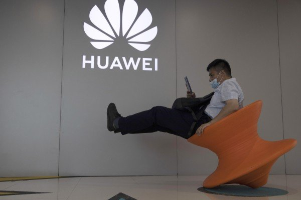 A man wearing a mask to curb the spread of the coronavirus sits near a Huawei store logo in Beijing on Friday, July 31, 2020. Photo: AP