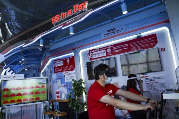 Staff demonstrate a VR cycling system during a media tour of SmarTone 5G Lab at Sky 100 at the International Commerce Centre in Hong Kong on May 1. Telecoms companies are betting on virtual and augmented reality to help recoup the costs of building 5G networks. Photo: SCMP/Sam Tsang