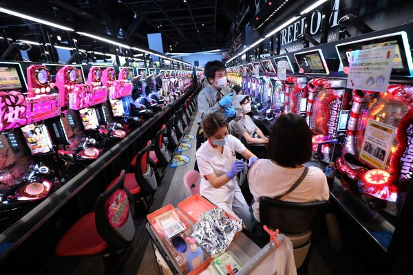 A health worker administers a dose of Covid-19 vaccine to a person in a pachinko arcade in Osaka on Tuesday. Photo: AFP