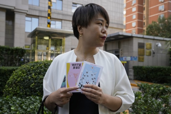 """Teresa Xu holds up cards one of which reads """"My Womb, My Choice"""" before attending a court session in Beijing on Friday. Photo: AP"""