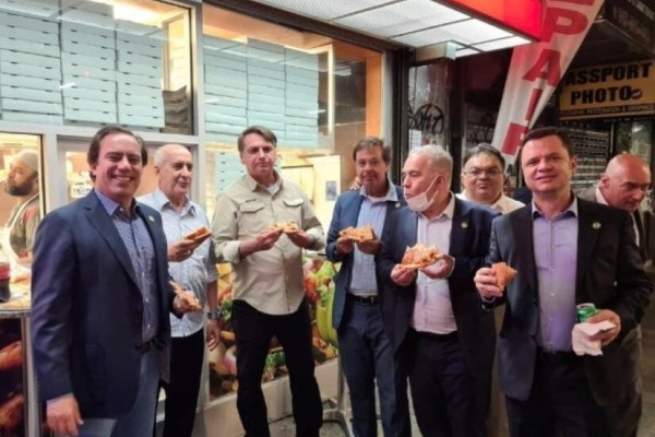 Brazil's President Jair Bolsonaro (centre) eats pizza with members of his delegation in New York on Saturday. Photo: Gilson Machado Neto via Instagram/Reuters