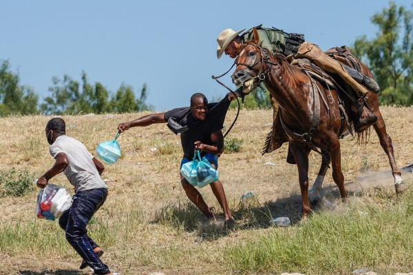 US Border Patrol agent on horseback tries to stop a Haitian migrant from entering an encampment on the banks of the Rio Grande in Del Rio, Texas, on Sunday. Photo: AFP