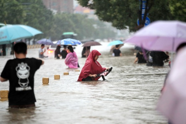 People wade down a flooded road after record downpours in Zhengzhou city in central China's Henan province, on July 20, 2021. Photo: Barcroft Media via Getty Images