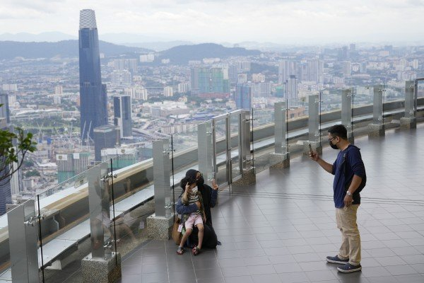 Tourists take photos on an observation deck at the Kuala Lumpur Tower in Malaysia. Photo: AP