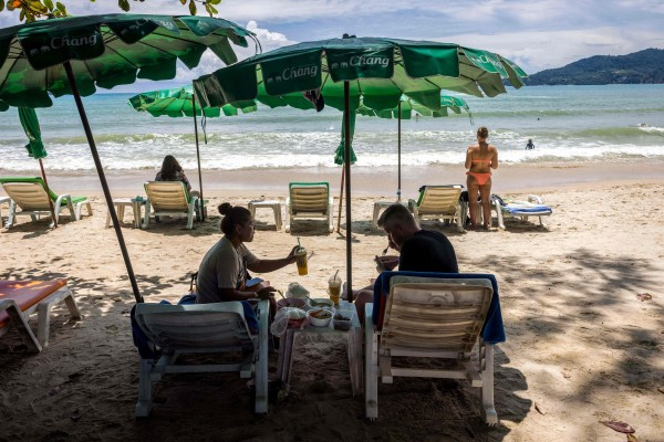 People under the shade of a beach umbrella in Phuket, Thailand. Photo: AFP