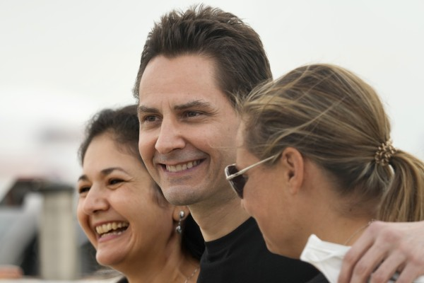 Michael Kovrig embraces his wife Vina Nadjibulla, left, and sister Ariana Botha after arriving at Pearson International Airport in Toronto on September 25. Photo: The Canadian Press via AP