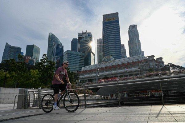 A man cycles past the city skyline in Singapore on Wednesday. Photo: AFP