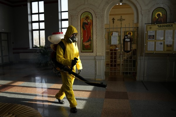A Russian emergency worker disinfects an area inside Savyolovsky railway station in Moscow. Photo: AP