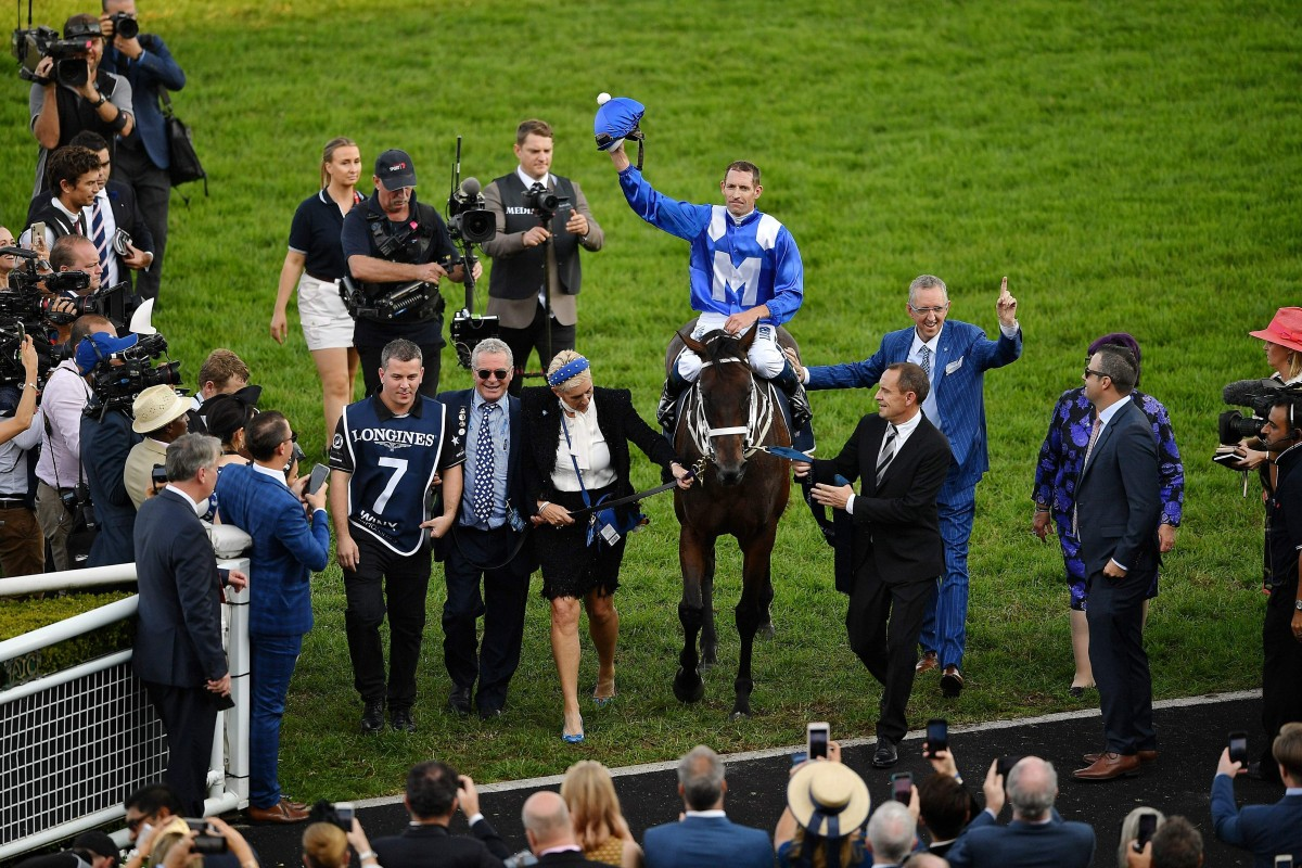 Jockey Hugh Bowman celebrates on the back of champion racehorse Winx after her final race to victory in the Longines Queen Elizabeth Stakes. Photo: AFP