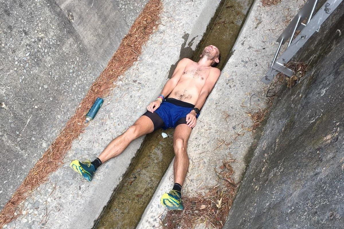 John Ellis squeezes into a catchwater during the Lantau Trail 70 trail race to cool down. Photo: Doug Treasure