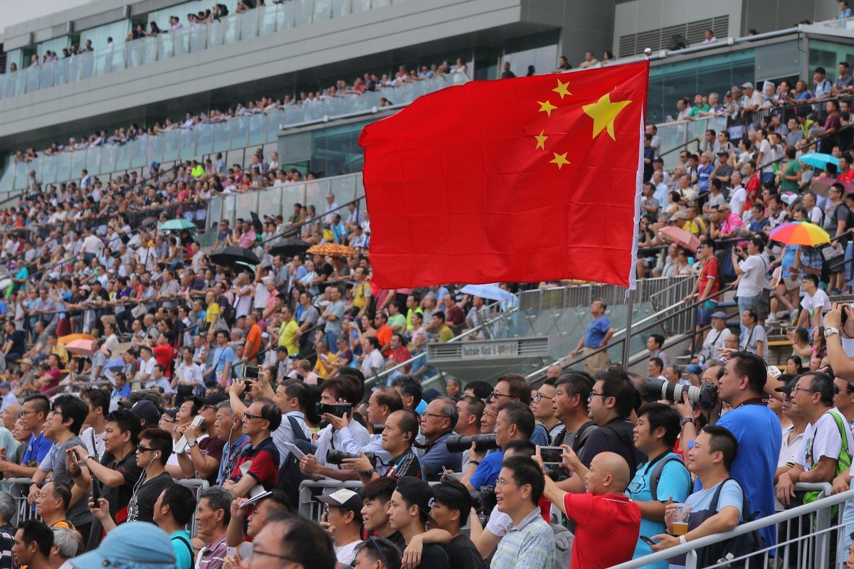 A fan raises a Chinese flag at Sha Tin's season opening meeting on Sunday. Photos: Kenneth Chan