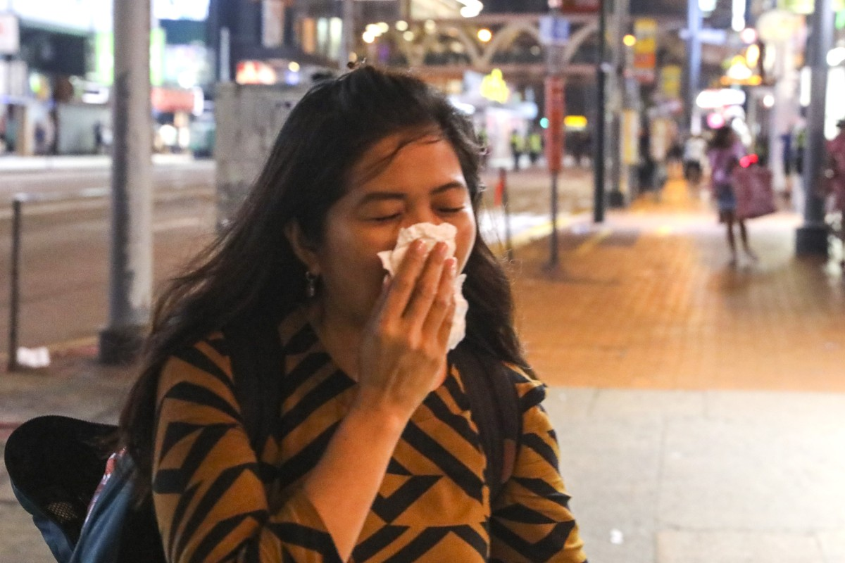 A woman reacts to tear gas in Causeway Bay where railings have been removed by anti-government protesters. Photo: K. Y. Cheng