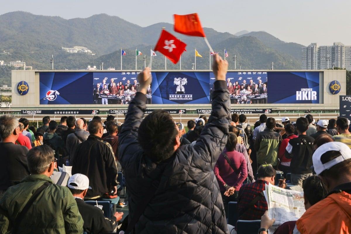 A racing fan waves the flags of Hong Kong and China during the Hong Kong International Races. Photo: Sam Tsang