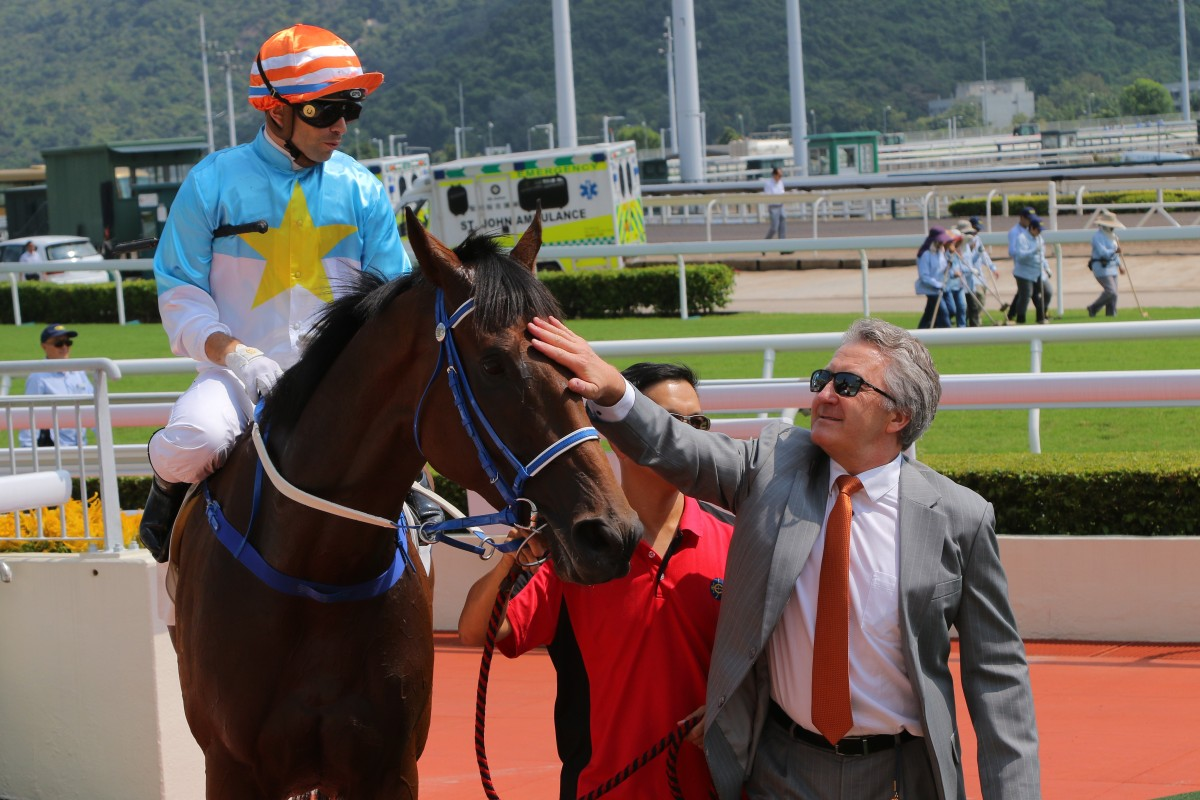 David Ferraris gives Blazing Partners a pat after his win under jockey Umberto Rispoli. Photos: Kenneth Chan
