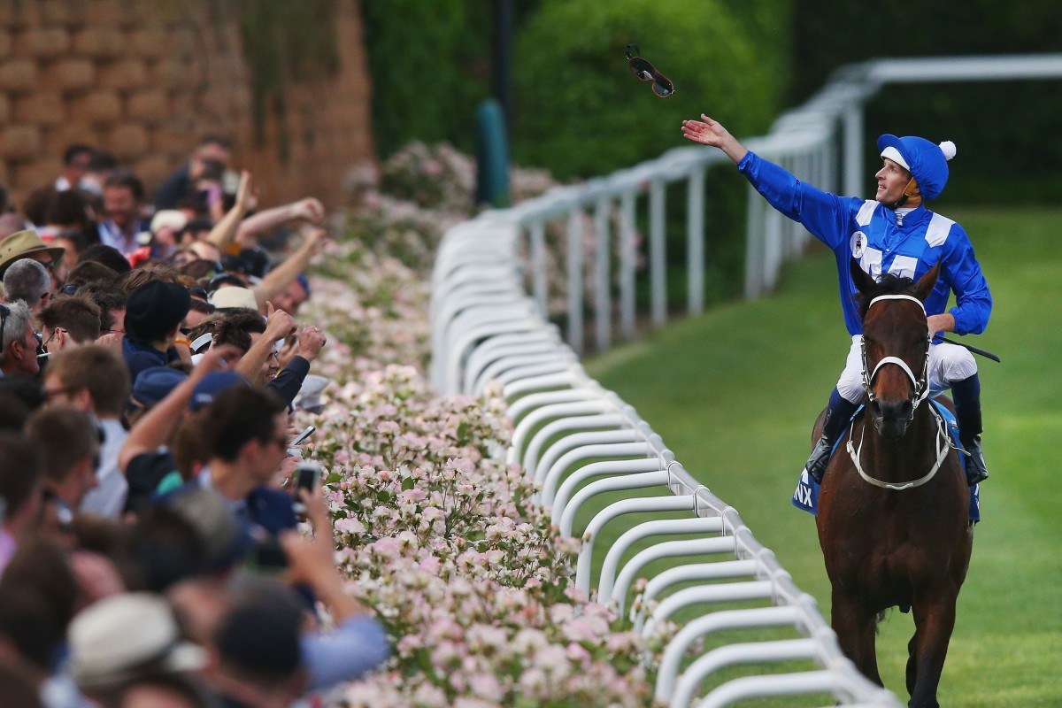 Hugh Bowman throws his goggles into the crowd after winning the 2015 Cox Plate with Winx. Photo: Michael Dodge/Getty Images