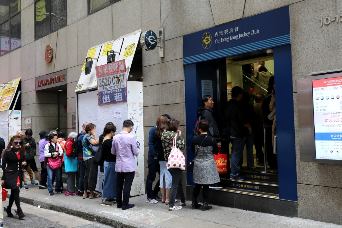 Gamblers line up at a Hong Kong Jockey Club off-course betting branch in Central. Photo: SCMP/Dickson Lee