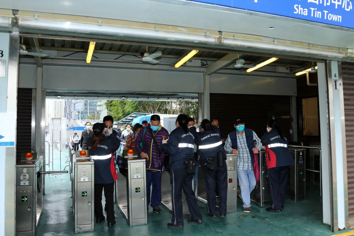 Security guards temperature screen customers at the entrance to Sha Tin racecourse. Photo: Kenneth Chan
