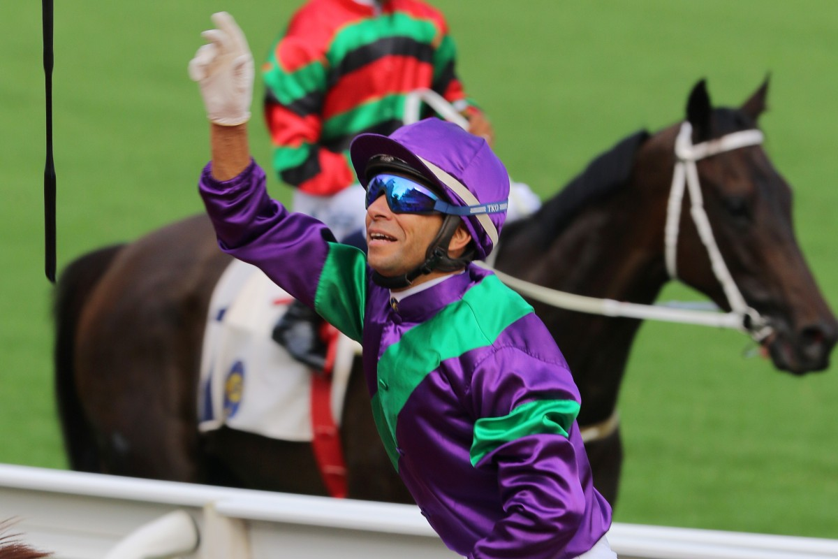 Joao Moreira celebrates his opening-day win aboard Excellent Proposal with his customary whip throw. Photos: Kenneth Chan