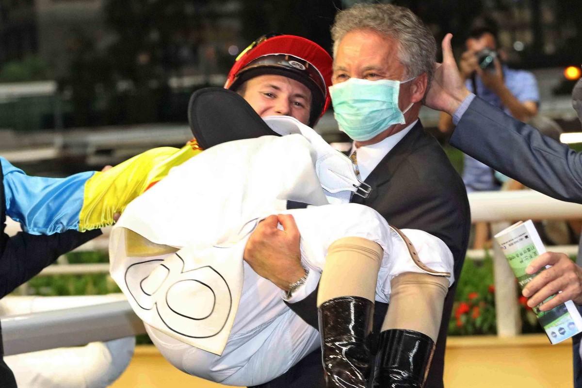 Trainer David Ferraris lifts up son Luke after the 19-year-old rode his first Hong Kong winner aboard Go Ballistic. Photos: Kenneth Chan
